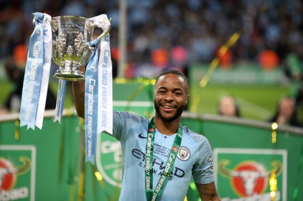 Raheem Sterling lifts the League Cup trophy